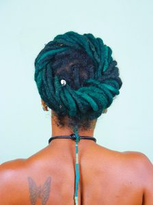 back view of woman with locs in a halo hairstyle